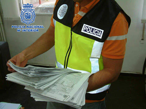 Un policía con documentación sobre un fraude a la Seguridad Social.