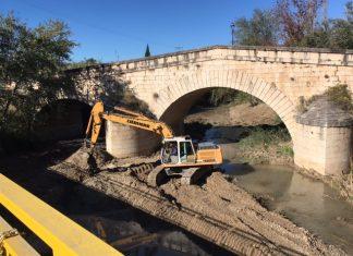 Maquinaria trabajando en el cauce del río a la altura de los puentes.