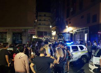 Jóvenes en la calle tras el desalojo del pub por exceso de aforo y ruido.