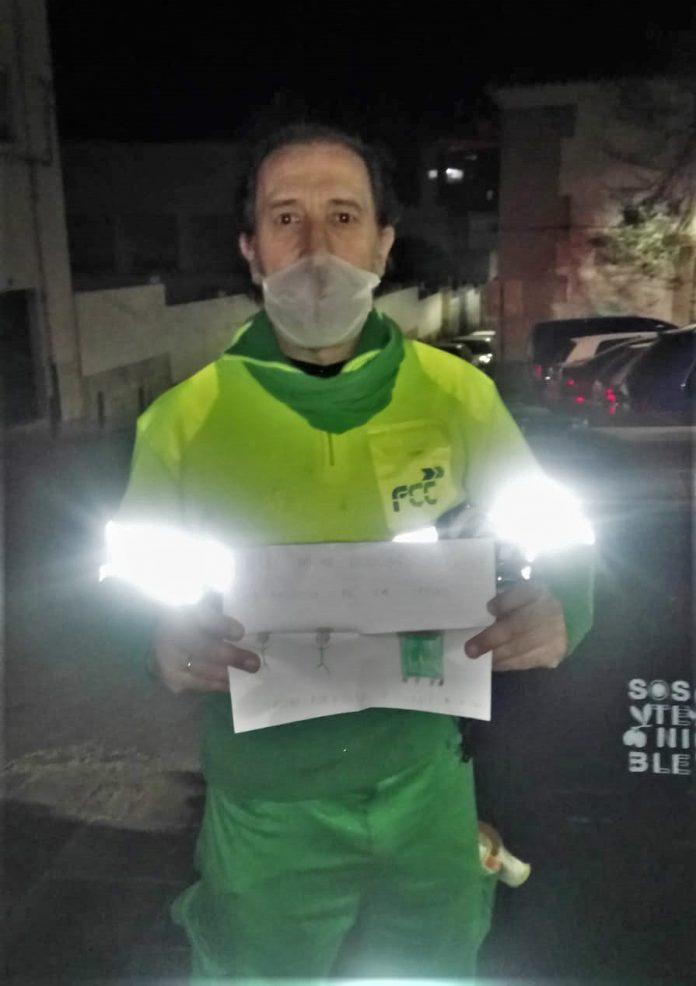 José Carlos con la carta que les ha pegado unos niños en uno de los contenedores.